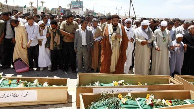Libyans attend the funeral of people killed in air strikes by coalition forces last night, at the martyrs' cemetery in Tripoli on Saturday.