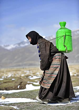 A Tibetan woman carries a plastic bottle of water on her back in Naqu in May 2011. (Rooney Chen/Reuters)