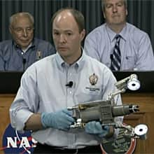 NASA's Benjamin Reed demonstrates one of the new tools that Dextre will use as NASA colleague Frank Cepollina, left, and the Canadian Space Agency's Mathieu Caron, right, look on.