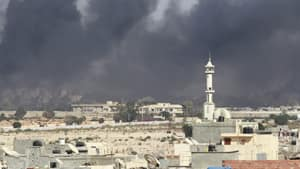 Smoke rises above downtown Tripoli following fighting at Bab Al-Aziziya compound.