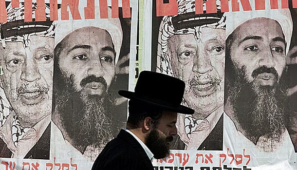 An ultra-Orthodox Jew passes a poster depicting Osama bin Laden and Palestinian President Yasser Arafat that reads: \
