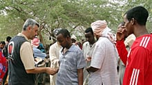 A Yardimeli representative hands out cash to a refugee in the Dadaab camp. The Turkish charity says it's helped thousands through cash and food handouts in recent days.