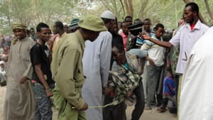 Crowd control in Dadaab: security officers use sticks and hide-covered whips to contain restless refugees in line for cash handouts from a Turkish charity.