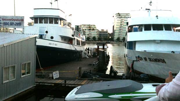 Investigators on a dock in a False Creek marina examine remains found in a shoe there Tuesday evening.