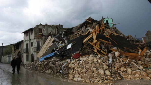 People walk past collapsed buildings near L'Aquila, Italy in after an deadly earthquake in April 2009. Seven scientists were found guilty of manslaughter Monday for failing to sufficiently warn residents of the quake.