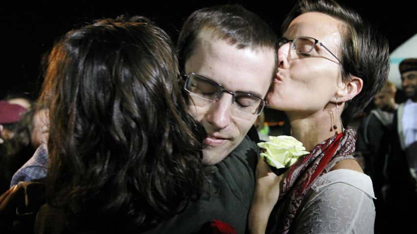 Shane Bauer, one of two U.S. hikers released from Iran on charges of espionage, is welcomed by fiance Sarah Shourd and other loved ones upon his arrival in Oman on Wednesday.