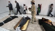 Libyan families view the body of slain Libyan leader Moammar Gadhafi inside a storage freezer in Misrata on Oct. 24. A Libyan official said the body was buried at dawn the next day.