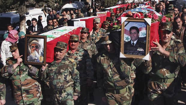 Syrian army officers carry the coffins of army members killed in an ambush on Nov. 17. Many fear the ongoing uprising in the country could descend into civil war.
