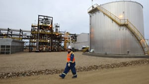 An oilfield worker walks past the Statoil oilsands facility near Conklin, Alta. A European Union proposal would officially label fuel from the oilsands as dirty because it results in 22 per cent more greenhouse gas emissions than conventional sources.