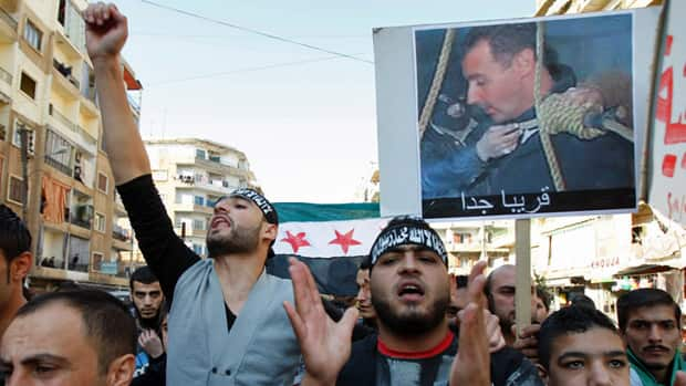 Lebanese and Syrians living in Lebanon chant slogans as they carry a Syrian flag and a picture depicting Syria's President Bashar al-Assad with a rope around his neck during a protest in Lebanon on Dec. 2, 2011.