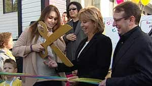 Sophie Tweed-Simmons, left, prepares to cut the ribbon at Sophie's Place, as Surrey Mayor Diane Watts, right, and rock star father Gene Simmons, centre, look on.