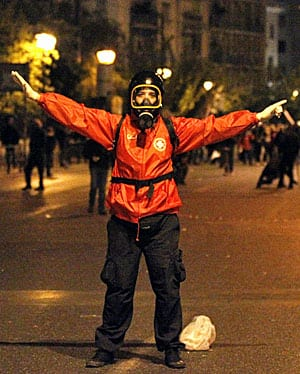 A medic stands between rioters and Athens police in November 2011, in just one of the many angry protests over proposed austerity that have convulsed the country in the past year.