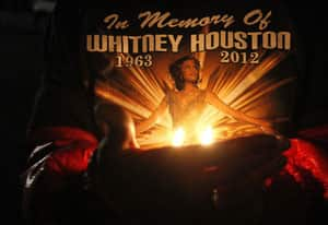 Whitney Houston fans held a candlelight vigil outside the Whigham Funeral Home, in Newark, N.J., where the late singer's body arrived Monday night.