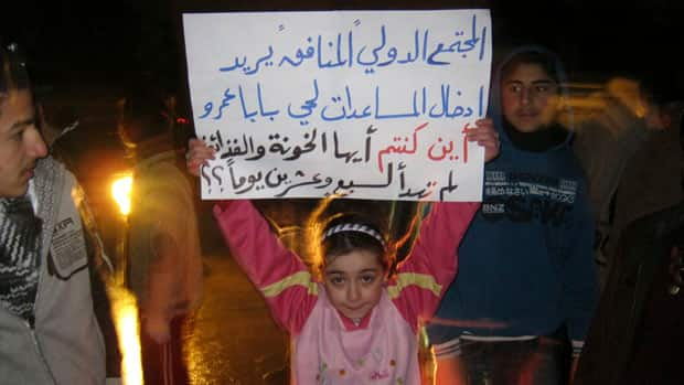A girl whose father was killed during the recent shelling on Baba Amr holds a placard at a protest in al-Qusour, Homs on Saturday.
