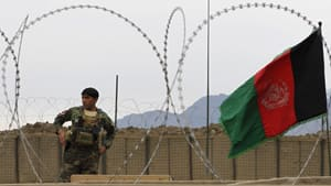 An Afghan National Army soldier stands near an Afghan national flag at Forward Operating Base Joyce in Kunar province, eastern Afghanistan. Security has been boosted at bases in the country following the shooting of 16 civilians on the weekend.