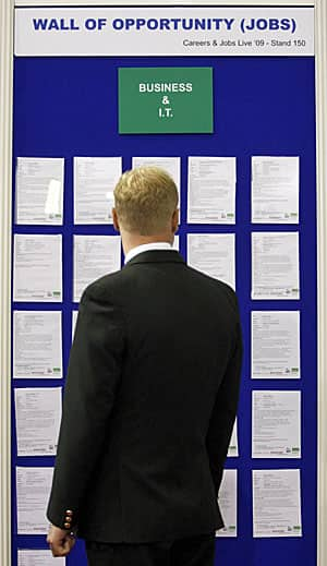 A job seeker scans the bulletin board at a jobs fair in London, U.K.