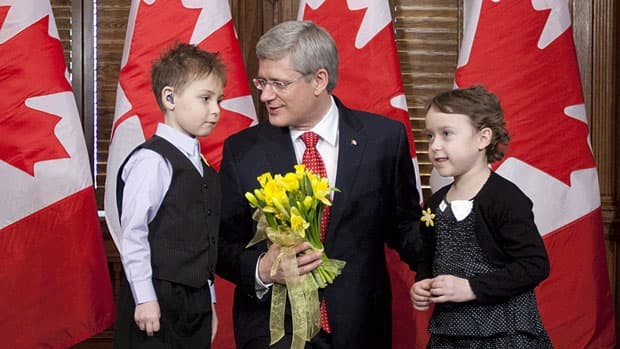 Prime Minister Stephen Harper is presented with a bouquet of daffodils in his office on April 3, to mark the Canadian Cancer Society's Daffodil Campaign. His government announced $12 million in funding for childhood cancer research on Wednesday.