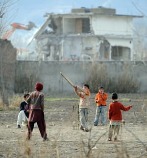 Children play near the former compound of Osama bin Laden, seen in the background, in Abbottabad, Pakistan.