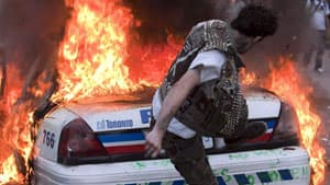 A man kicks a burning police car on June 26, 2010 during the G20 protests.
