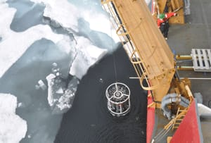 A crane lowers sample bottles into the Arctic Ocean to collect water from underneath the sea ice.
