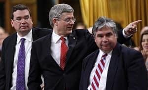 Prime Minister Stephen Harper, middle, Minister of Industry Christian Paradis, left, and Government House Leader Peter Van Loan are recognized during a vote Thursday.