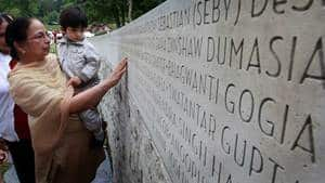 Jagit Grewal shows her two-year-old grandson Devin Grewal where her husband, Daljit Singh Grewal, and his grandfather's name is on a monument honouring those who died, during a memorial marking the 25th anniversary of the Air India bombing in Vancouver on June 23, 2010.