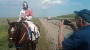 It's not every day you see a knight on horseback riding along a rural highway.