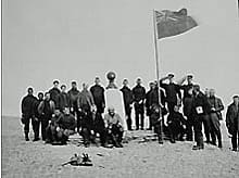 A flag is raised on Aug. 15, 1904, at a Franklin monument on Beechey Island, where the remains of three sailors from the Franklin expedition were excavated several decades later.