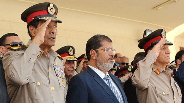 Egypt's President Mohamed Morsi, centre, demanded the retirement of the head of the military council Field Marshal Hussein Tantawi, left, and Egyptian armed forces Chief of Staff Sami Anan, right.