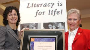 Senator Joyce Fairbairn, right, is shown receiving a special recognition award for her work on literacy from Canada Post in 2002. She will be on sick leave starting in September.