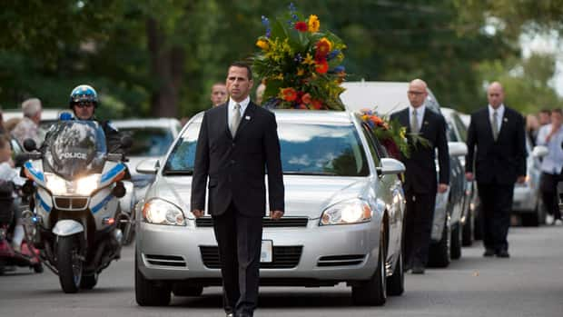 Denis Blanchette's funeral cortege arrives at St. Donat Church for his state-sponsored funeral in Montreal on Monday afternoon. People of fame and power attended the ceremony for the lighting technician.