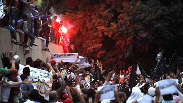 Egyptian protesters climb the walls of the U.S. Embassy during protests in Cairo on Sept. 11.