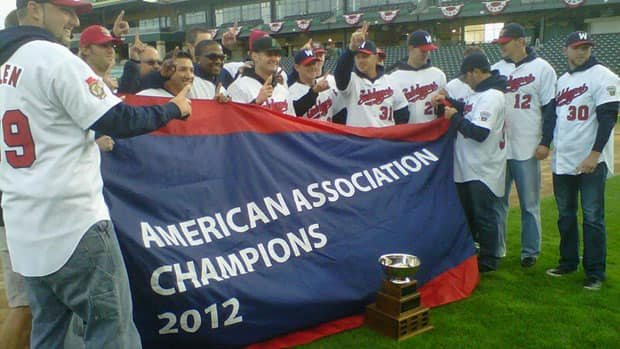 Members of the Winnipeg Goldeyes hold up the American Association Championship banner at Shaw Park on Sunday evening.