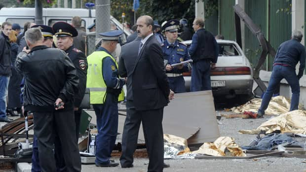 Law enforcement authorities work at the site of the crash where a drunk driver killed seven people at a bus stop in Moscow, Russia.