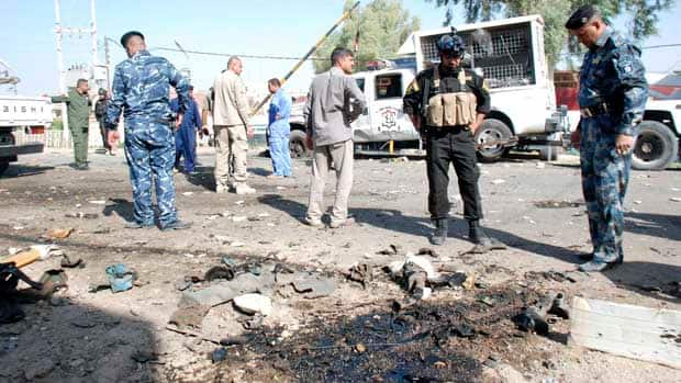 Iraqi security personnel stand at the site of a bomb attack in Kut, 150 kilometres southeast of Baghdad. A suicide bomber in a car blew himself up in the city, killing four police officers.