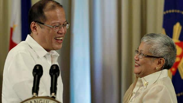 Philippine President Benigno Aquino III, left, shakes hands with Presidential adviser on the peace process, Secretary Teresita Quintos-Deles after Sunday's announcement.