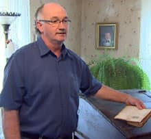 Ronnie MacInnis stands by his great-grandfather's desk and paybook.