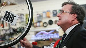 Finance Minister Jim Flaherty examines a bicycle wheel after his news conference at a bike shop in Ottawa Thursday to discuss measures in his second budget implementation bill.
