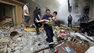 A Lebanese first responder carries an injured boy at the scene of an explosion in Beirut that killed at least eight people and injured dozens more.
