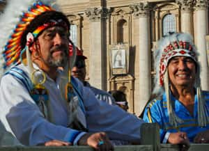 Two men in feathered headdresses wait for the start of the canonization ceremony in St. Peter's Square.