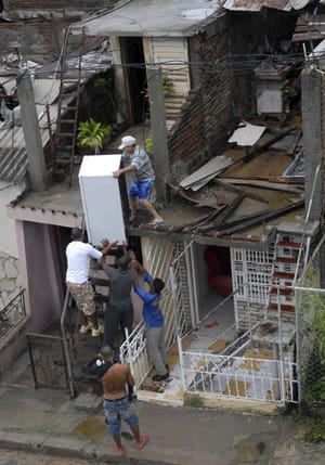 A resident  salvages a refrigerator from his damaged house, with the help of other men, after Hurricane Sandy hit Santiago de Cuba on Thursday. Many homes were damaged or destroyed in the city of 500,000 people.