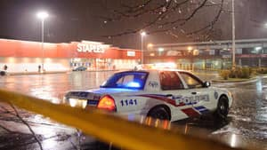 Toronto police sit at a taped-off Staples outlet parking lot after strong storm winds caused a sign to fall, killing a woman in Toronto on Monday.