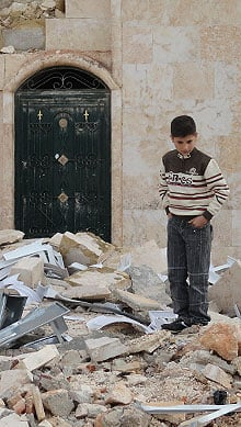 A Syrian boy walks through rubble where a field clinic once stood before it was bombed by regime forces in Anadan, just outside Aleppo.