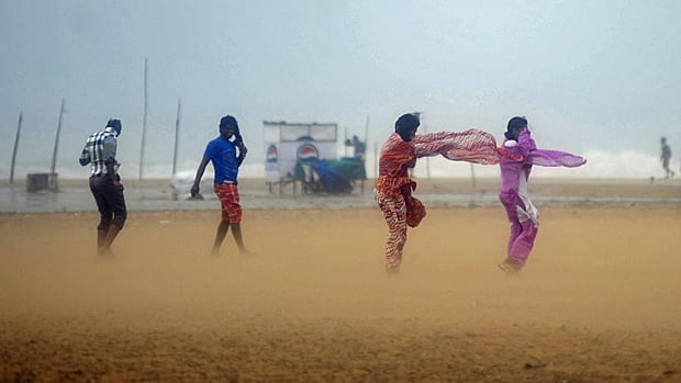 Women shield their faces during strong winds at Marina Beach in the southern Indian city of Chennai Wednesday. The Chennai port on the southeast coast has stopped cargo operations after a cyclone warning.