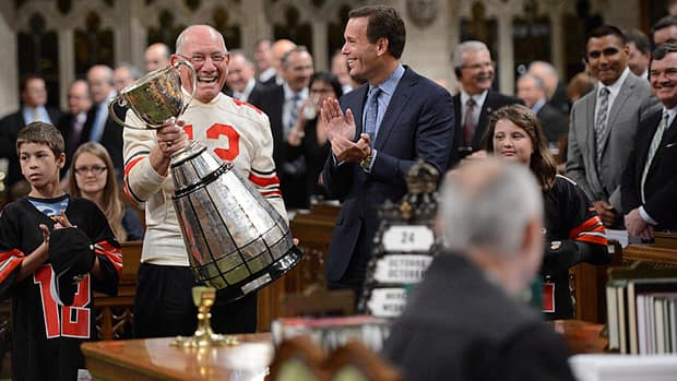 The Grey Cup is making its way through Canada on its 100th anniversary tour. Here, former Ottawa Rough Rider and three-time Grey Cup champion quarterback Russ Jackson carries it through the House of Commons on Parliament Hill in Ottawa on Oct. 24. The cup will be at Bayfront Park in Hamilton Saturday.