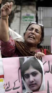 A Pakistani activist chants slogan Saturday as she holds a portrait of Malala Yousafzai in Lahore.