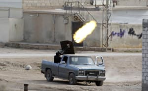 A Free Syrian Army fighter fires an anti-aircraft artillery weapon during an air strike in the Syrian town of Ras al-Ain, as seen from the Turkish side of the border, Nov. 13. A Syrian warplane struck homes in the town of Ras al-Ain on Tuesday, pursuing an aerial bombardment to force out rebels, a Reuters witness and refugees said.