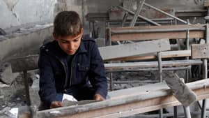 A Syrian boy reads a torn paper inside his destroyed school classroom, in Aleppo, Syria, on Thursday.
