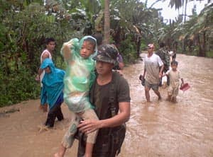 A soldier carries a boy along a flooded area in Compostela Valley, southern Philippines.