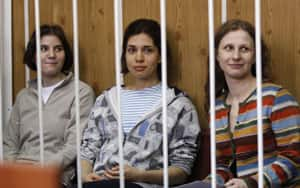 Yekaterina Samutsevich, left, Nadezhda Tolokonnikova and Maria Alyokhina, three members of the Russian feminist punk group Pussy Riot, sit behind bars before a court hearing in Moscow on July 20, 2012. The women's protest in Moscow's Christ the Saviour Cathedral and their subsequent arrest inspired demonstrations of solidarity around the world and reinvigorated the anti-Putin protest movement at home.